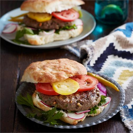 Spiced lamb pine nut burgers with tahini yoghurt in a serving dish