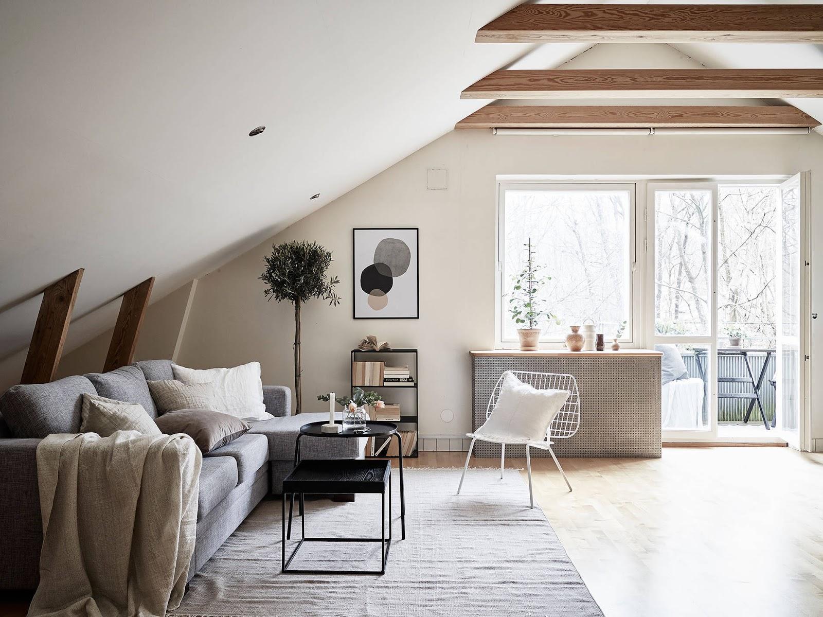 szara kanapa w salonie, skośne ściany w salonie