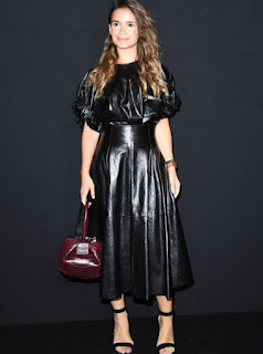 Mira Duma at Giorgio Armani Prive Haute Couture 2016/17 show in black leather short sleeve top black leather midi skirt and with an oxblood handbag