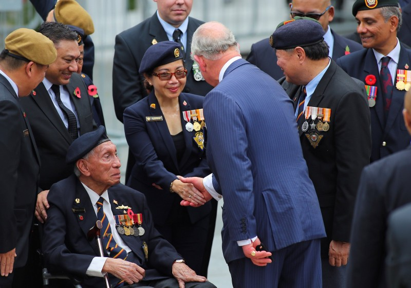 Britain's Prince Charles speaks with military veterans after laying a wreath at the Cenotaph war memorial in Singapore October 31, 2017.