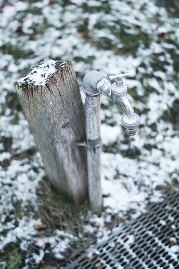 Blog + Fotografie by it's me! - Draussen - Frau Frieda sucht Schnee, verschneiter Holzpflock mit Wasserhahn