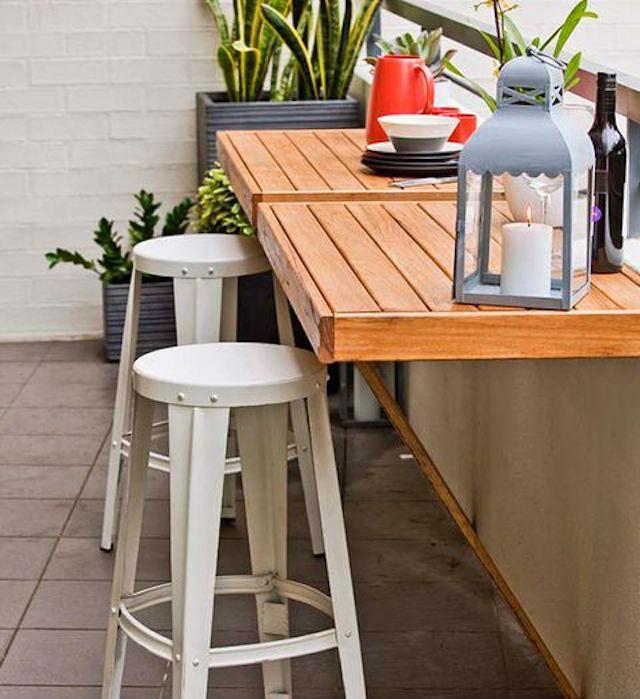 Balcón con banco de madera en la barandilla para comer