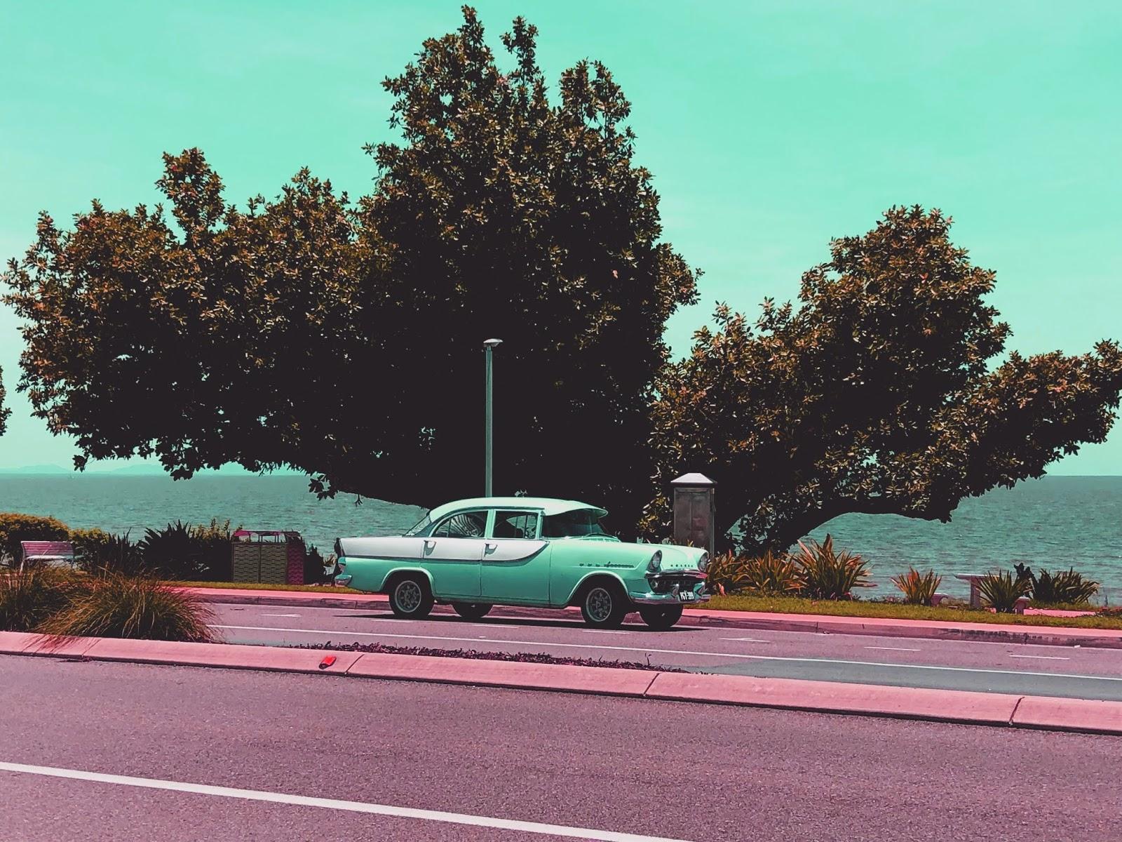 Kolekcjonerski stary samochód na ulicy w australijskim mieście Cardwell. W tle Morze Koralowe.