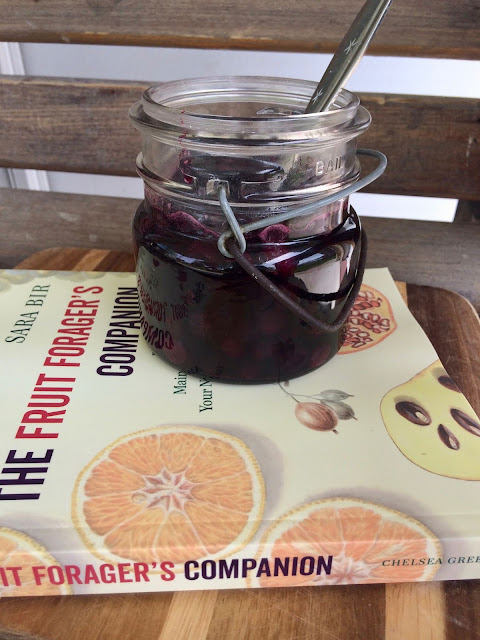 Jar of roasted maple blueberries with cookbook and spoon.