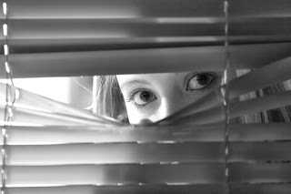 Woman Peaking Past Blinds