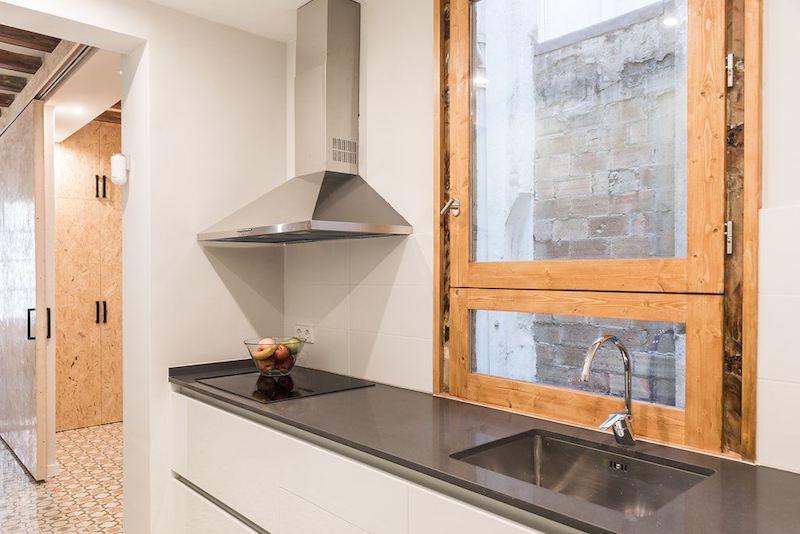 Apartamento con muebles de cartón y la instalación vista. Cocina mini y puerta de osb al fondo.