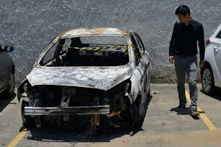 A man looks at the burned-out rental car of missing Greek ambassador to Brazil Kyriakos Amiridis