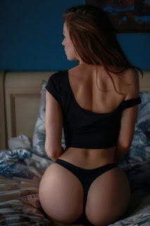 red haired escort girl sitting on bed