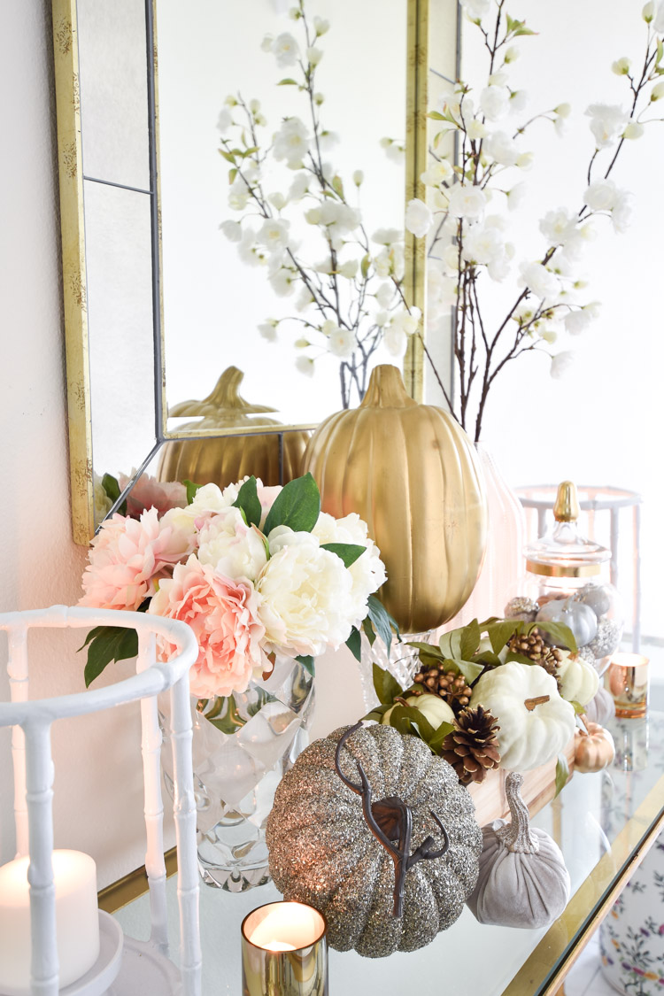 Faux florals, white, gold and silver pumpkins and white cherry blossoms create a feminine fall decor vignette.