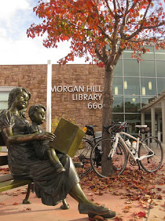 Statue of a woman reading a book to a young boy on her lap in front of the Morgan Hill Library, Morgan Hill, California