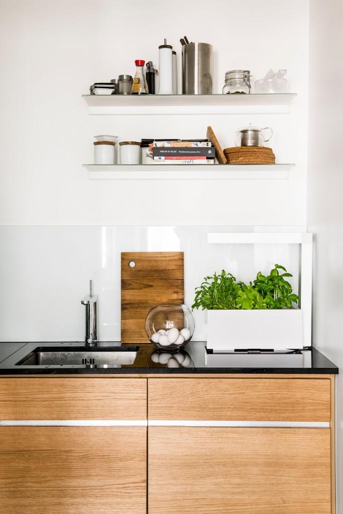 cocina madera con encimera negra y estanterías voladas