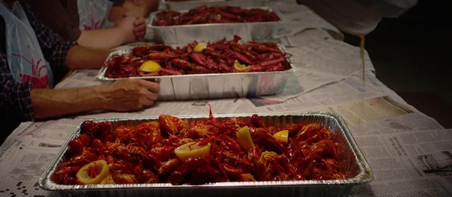 tres enormes bandejas llenas de cangrejos de rió con una salsa roja y limones