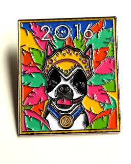 A rectangular (portrait orientation) metal and enamel pin. The subject is the Ravelry mascot, Bob the dog, who has a white face with black patches over his eyes and muzzle. He is wearing a mardi gras headpiece and is surrounded by tropical coloured leaves or feathers. The leaves are orange, hot pink, yellow and aqua. Bob is wearing a blue collar with a pendant in the shape of a yellow ball of yarn.