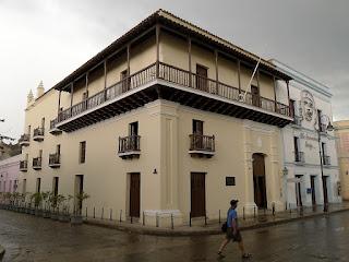 Geburtshaus des Freiheitshelden Ignacio Agramonte, viele Balkone mit Holzbalustraden; im Hintergrund weiteres Haus mit Bildnis von Che Guevara.