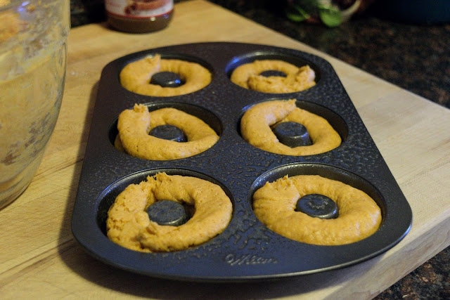 A greased donut baking pan with the batter squeezed into it.