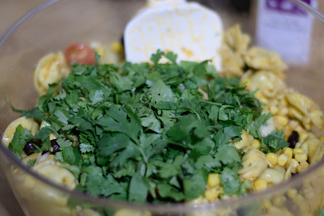 Chopped cilantro in a mixing bowl with the Mexican Pasta Salad.