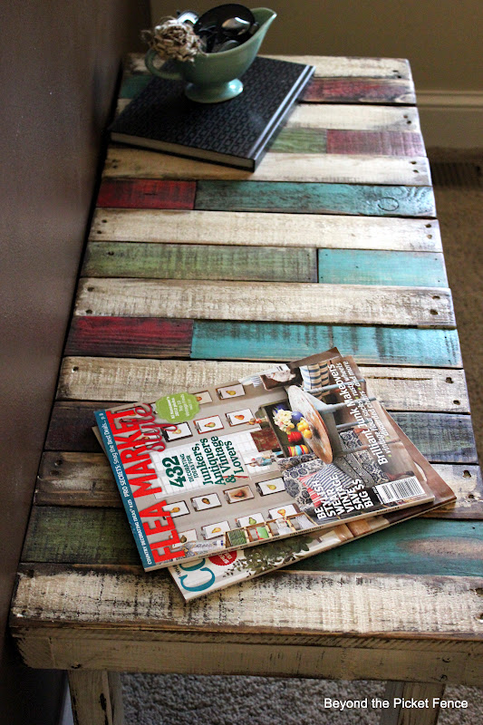 This pallet bench is stained with colorful tones for a super creative look