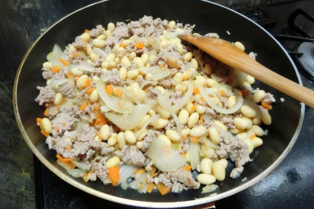 ひき肉の色が変わったらキッチンペーパーで軽くフライパンの中にある余分な油を拭き取り、水気をきった水煮大豆を加え、1分ほど炒めます。