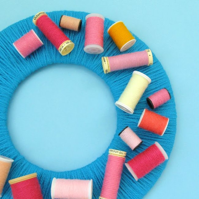 Colourful yarn-wrapped wreath decorated with upcycled sewing reels