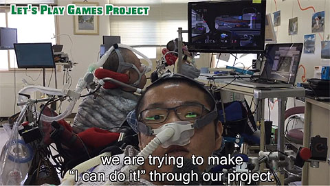 "Man with breathing apparatus in front of a man in a wheelchair playing a video game. Subtitles read, ""we are trying to make I can do it through our project."""