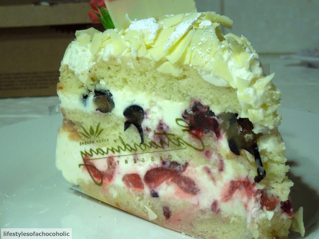 close up of a slice of White Chocolate cake with fresh berries on white plate