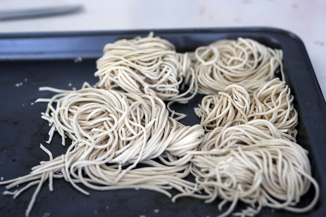A tray of freshly cut ramen noodles gathered in bundles.