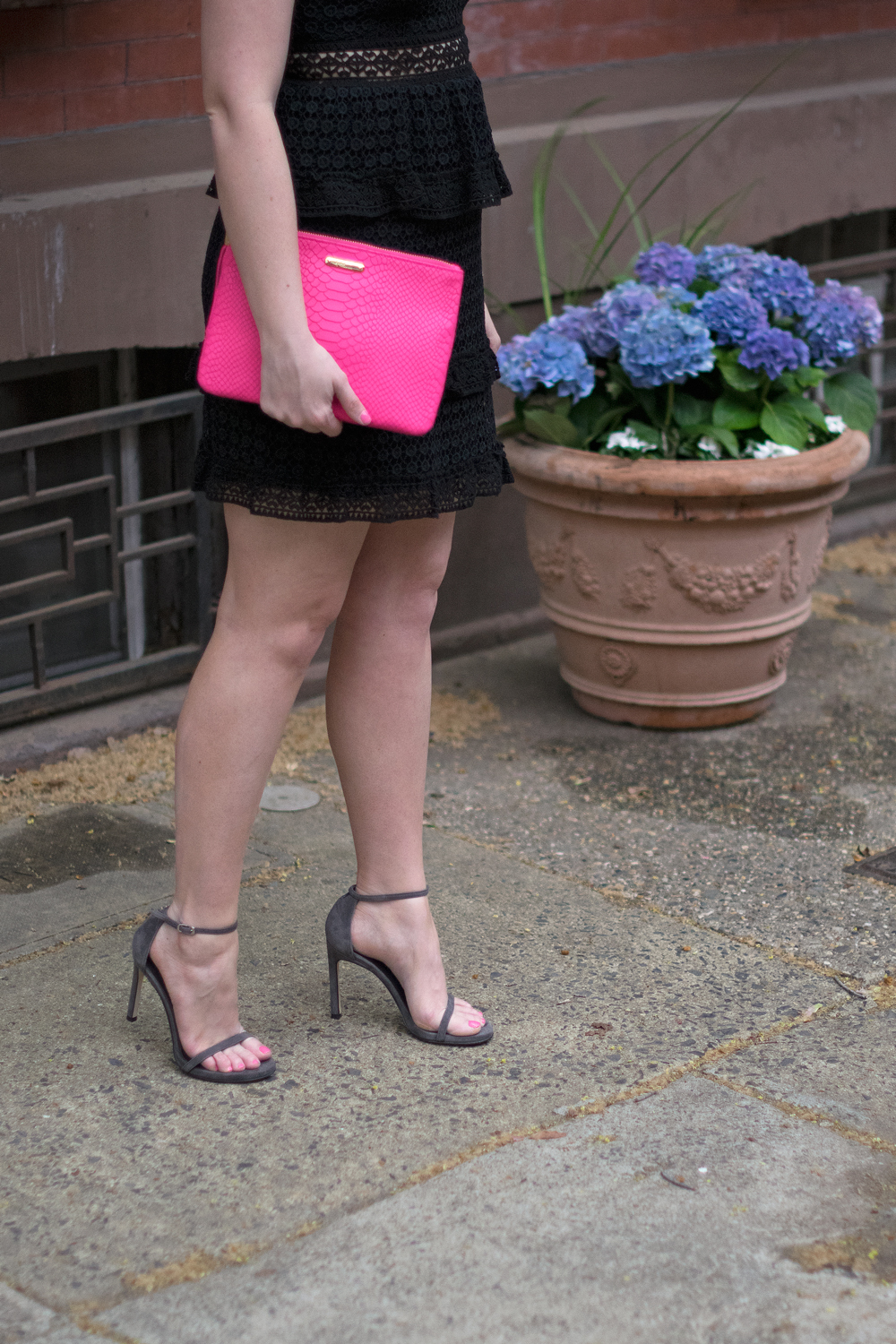 Pink clutch with black and grey outfit.