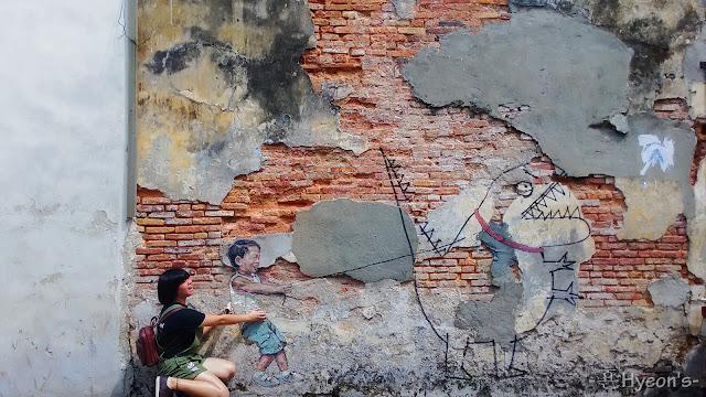 little boy with pet dinosaur street art penang