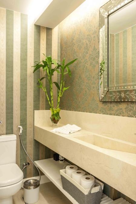 Lavabo com dois papéis de parede diferentes, um floral e um listrado.