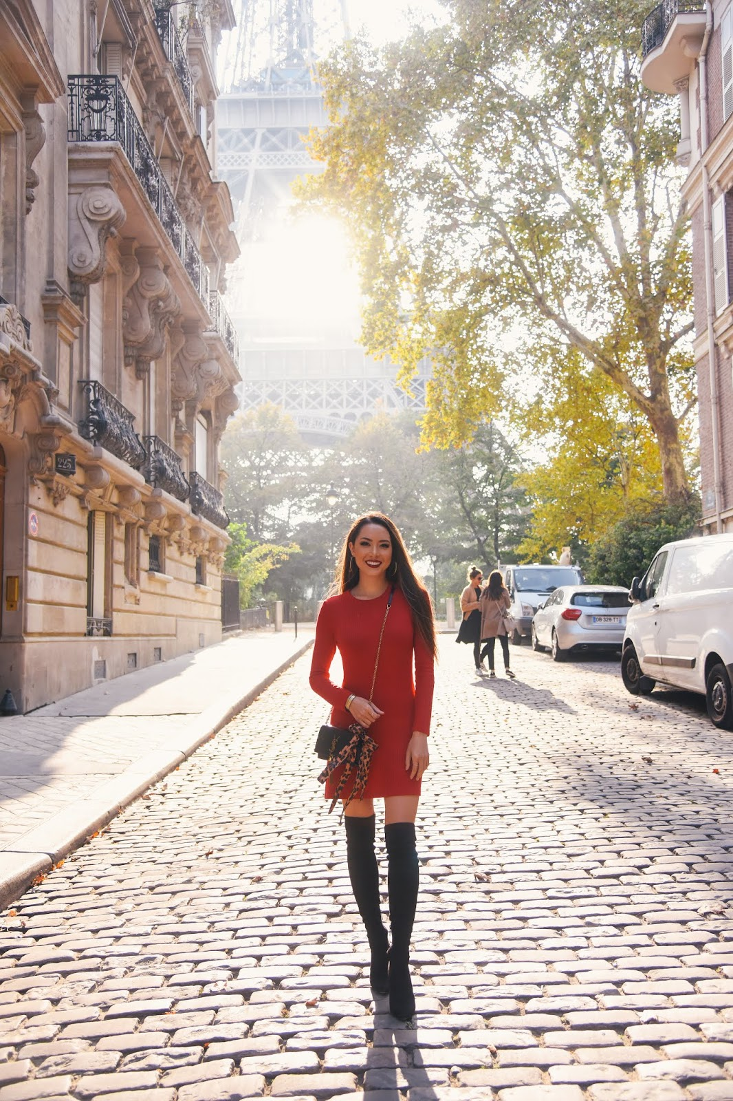 brunette in red dress and over the knee boots by eiffel tower in paris