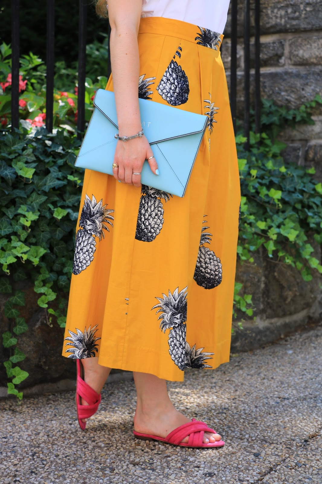 Fashion blogger Kathleen Harper wearing a pineapple skirt with pink slides