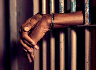 Black man in jail with hand out