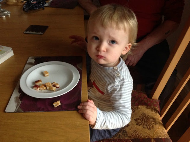 toddler sat at table eating