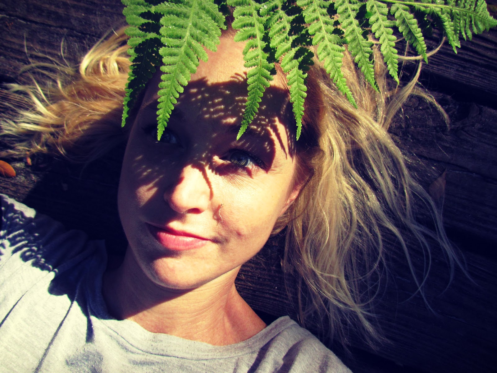 Blonde Woman Earthing on a Wooden Boardwalk in Nature With a Fern Leaf Headdress While Hiking
