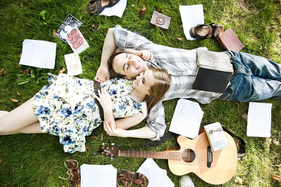 Engagement photo of a couple laying on the grass, surrounded by books, sheet music, and a guitar