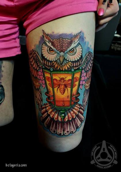 Este es un tatuaje de farol antiguo con búho colorido y una mariposa