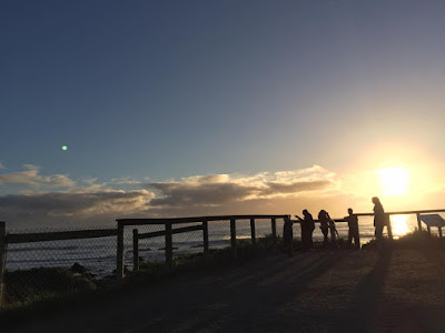 A view over the Pacific from near San Simeon at Sunset on New Years Eve 2016. To the right people stand silohuetted against the sun standing against a wooden fence. To the left of the picture the sky is a deep dark blue and a first cresent of the moon can be seen setting towards the darkening horizon.