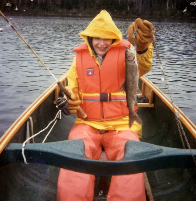 woman in a canoe wearing orange and yellow fishing outfit and  holding a fish