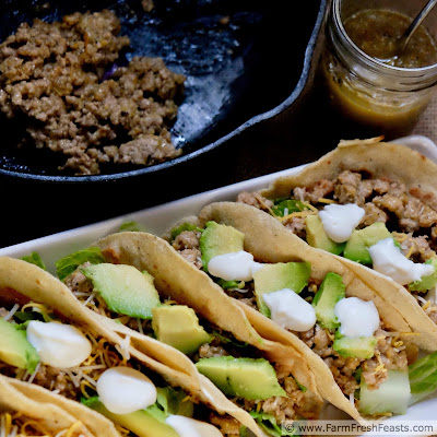 image of tray of salsa verde pork tacos with skillet of taco mixture and extra salsa
