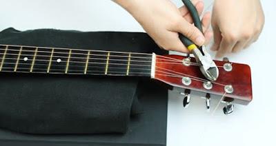 Memotong sisa senar gitar dengan tang potong