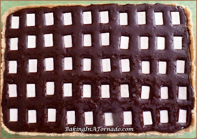 Kit Kat Brownie Bars: Mini white chocolate covered Kit Cats baked in a brownie center with a shortbread crust | Recipe developed by BakingInATornado.com | #recipe #bake #chocolate