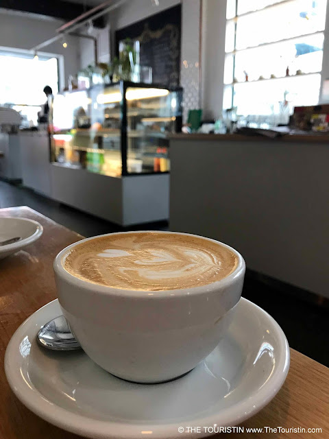 Flat White espresso drink in a white cup on a wooden table with a glass counter in the background.