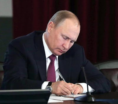 Vladimir Putin sign documents.