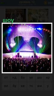 на сцене происходит представление лазерного шоу перед зрителями