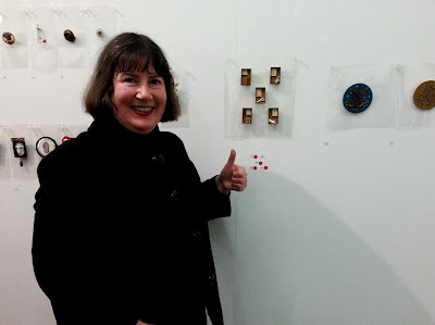 Woman looking happy and making a thumbs up sign in front of five brooches with four red dots.