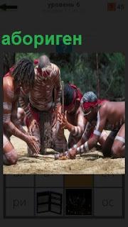 Несколько аборигенов склонились около одного, который добывает огонь палочкой