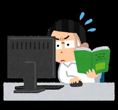 マニュアルを見ながらパソコンを操作する男性