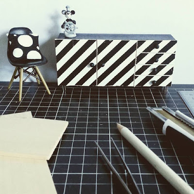 One-twelfth scale modern miniature sideboard with black and white striped front, next to an Eames chair with a black and white spotted cushion on it, on a cutting mat with various full-sized tools laid out on it.