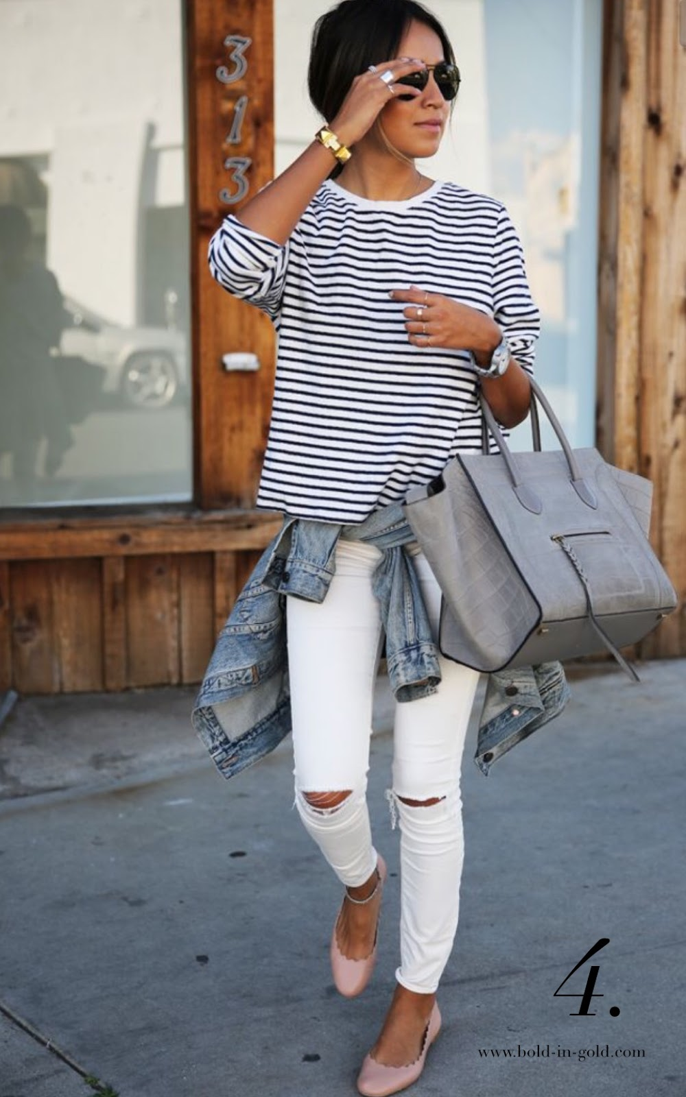 Woman wearing white ripped jeans with a striped t-shirt