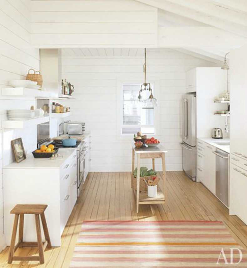 White modern cabinets and white wood plank walls give this Kitchen an airy and open feel.